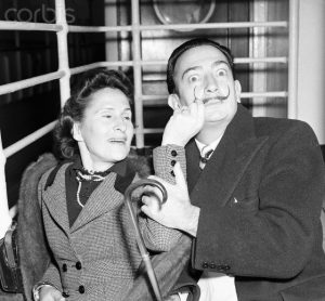 Original caption: 12/24/51-New York: Salvador Dali, surrealist painter, and his wife, Gala, arrive in New York, Dec. 24, aboard the Liner America. Dali, whose newly-regrown handlebars mustache is twirled by his playful spouse, returned to the U.S. after eight months abroad. The whimsical artist has had exhibitions in France, England and Spain. --- Image by © Bettmann/CORBIS